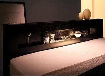 ヘッドボードの棚の上部から棚のギャラリーを照らすような間接照明が、部屋に仄かに広がる