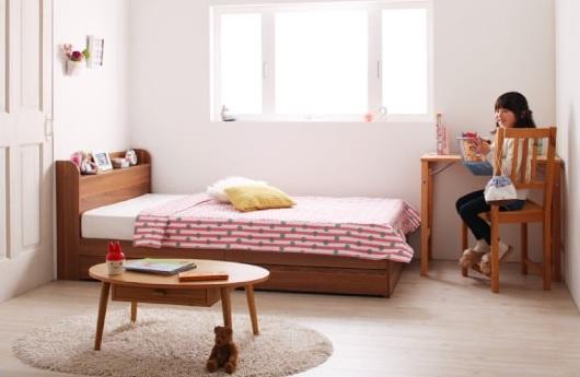 狭い部屋にショート丈の小さいベッドと、小さい丸型ラグのコーディネート