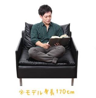 広い一人掛けソファーで胡坐をかいて読書