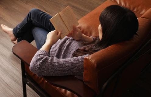 木肘ソファーで読書する